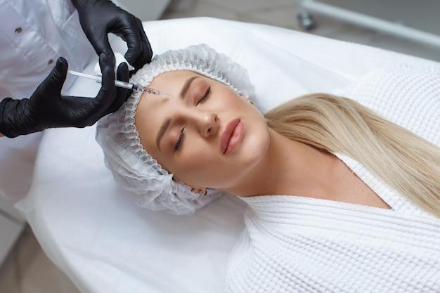 Vrouw krijgt cosmetische injectie van botox in de wang, close-up. vrouw in schoonheidssalon. kliniek voor plastische chirurgie.
