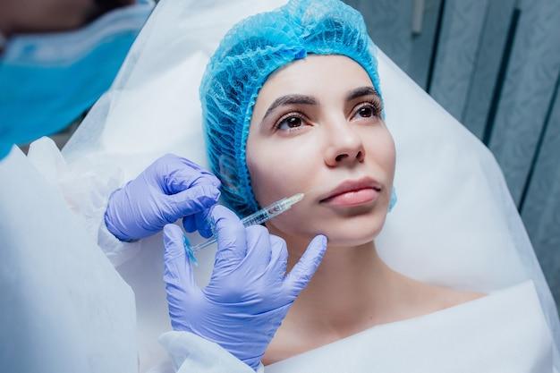Vrouw krijgt cosmetische injectie van botox in lip, close-up. vrouw in schoonheidssalon. kliniek voor plastische chirurgie