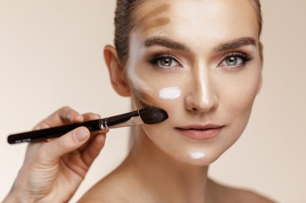 Vrouw krijgt een basis voor make-up