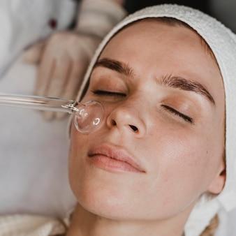 Vrouw krijgt een gezichtshuidbehandeling in het wellnesscentrum