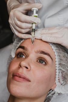 Vrouw krijgt een gezichtsschoonheidsinjectie in het wellnesscentrum