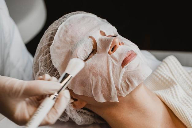 Vrouw krijgt een huidmaskerbehandeling in het wellnesscentrum