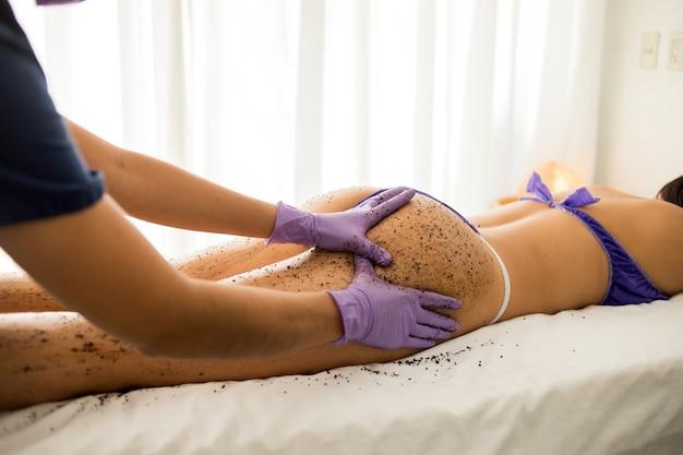 Vrouw krijgt een ontspannende scrubmassage van het hele lichaam in een spa