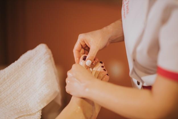 Vrouw krijgt een ontspannende voetmassagebehandeling in de spasalon