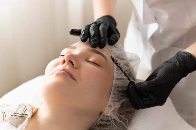 Vrouw krijgt een wenkbrauwbehandeling bij de schoonheidssalon