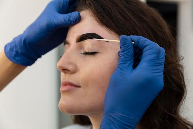 Vrouw krijgt een wenkbrauwbehandeling bij een schoonheidssalon