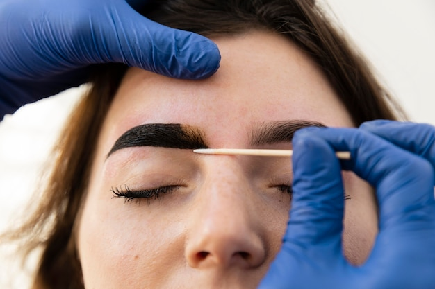 Vrouw krijgt een wenkbrauwbehandeling van een schoonheidsspecialiste