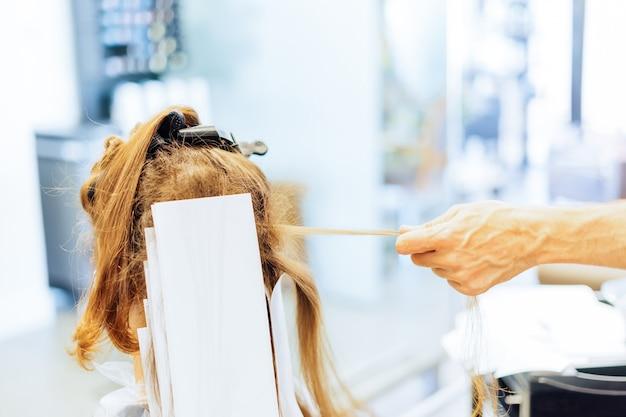 Vrouw krijgt highlights, hand trekt aan een haarlok bij de kapper