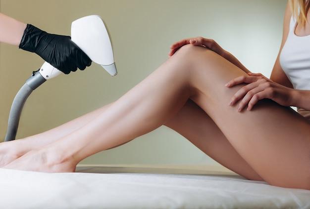 Vrouw krijgt laserbehandeling op haar benen in een schoonheidssalon. schoonheidsspecialist die laserepilatie doet aan haar cliënt.