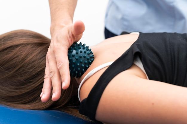 Vrouw krijgt massage van fysiotherapeut met bal op nek