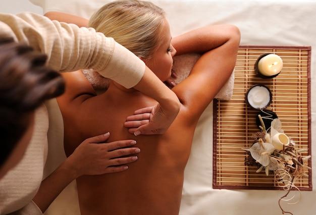 Vrouw krijgt ontspanningsmassage in de hoge hoekmening van de schoonheidssalon