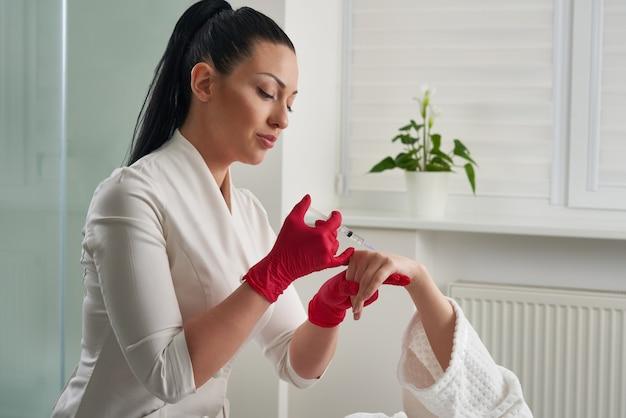 Vrouw krijgt verjongende vullerinjecties in haar hand. schoonheidsspecialiste die vuller in handhuid injecteren