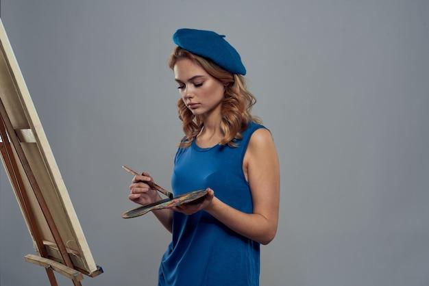 Vrouw kunstenaar blauw baret palet puttend uit ezel kunst creativiteit licht