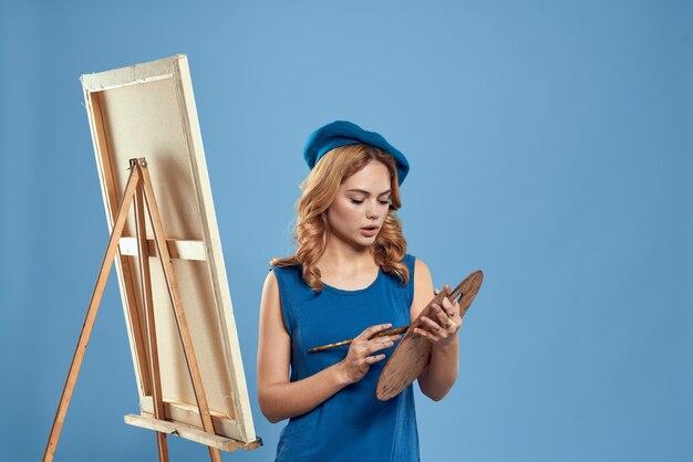Vrouw kunstenaar blauwe baret tekening palet ezel hobby creativiteit blauw