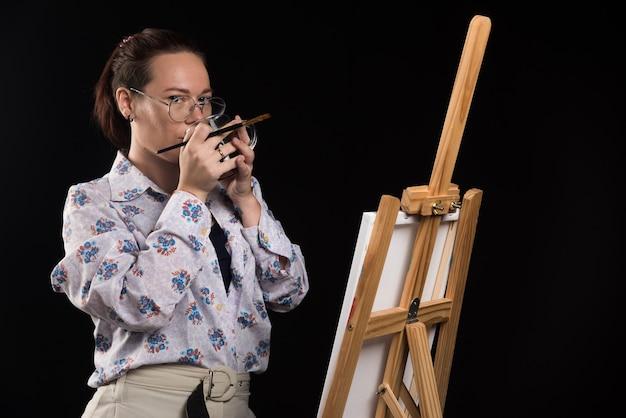 Vrouw kunstenaar borstel houden en het drinken van thee op zwarte achtergrond