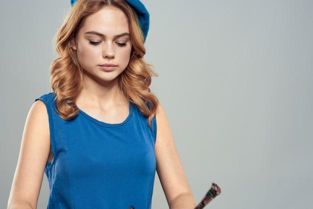 Vrouw kunstenaar borstel in hand blauwe baret jurk hobby kunst levensstijl lichte achtergrond