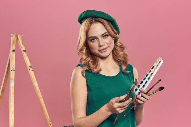 Vrouw kunstenaar groene baret aquarel penseel puttend uit een roze achtergrond