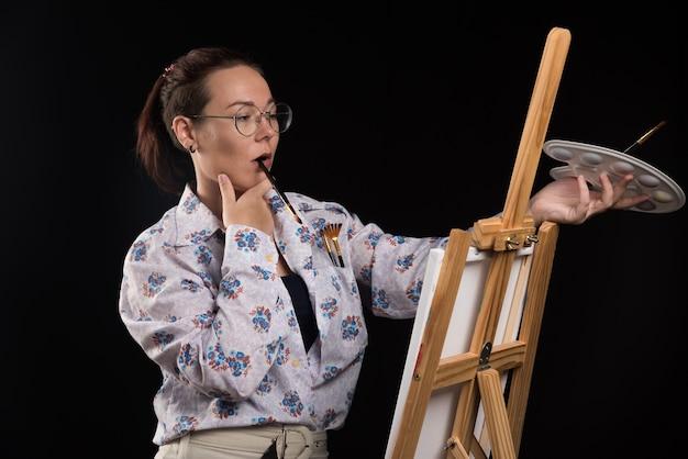Vrouw kunstenaar houdt een borstel in haar mond en denkt op zwarte achtergrond.