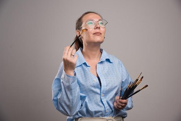 Vrouw kunstenaar houdt schilderij borstels in de buurt van haar gezicht op grijze achtergrond