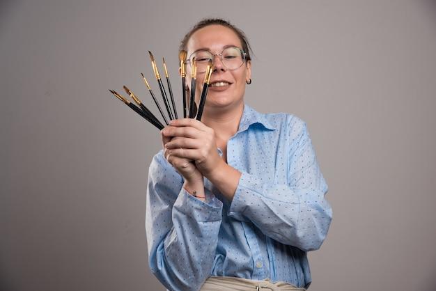 Vrouw kunstenaar houdt schilderij borstels op grijze achtergrond. hoge kwaliteit foto