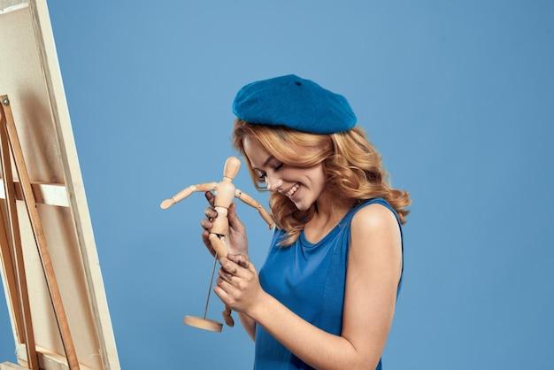 Vrouw kunstenaar houten mannequin ezel kunst in handen houden creatieve hobby blauwe achtergrond.