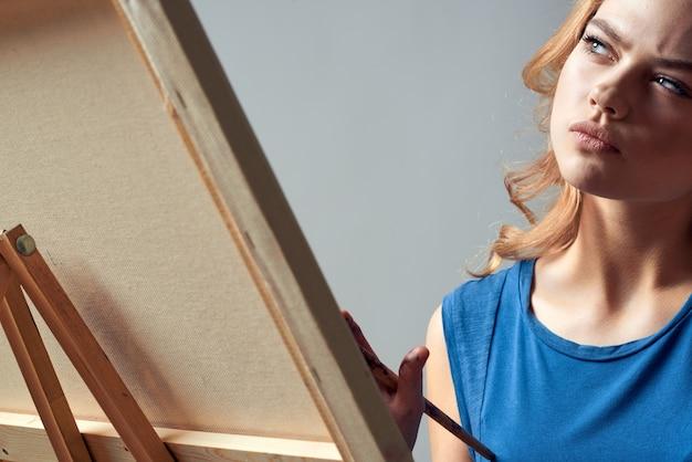 Vrouw kunstenaar met penseel verf op ezel kunst hobby licht.