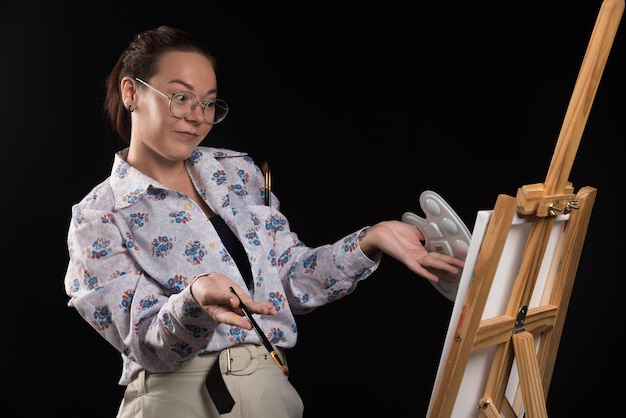 Vrouw kunstenaar penseel houden en kijken naar canvas op zwarte achtergrond