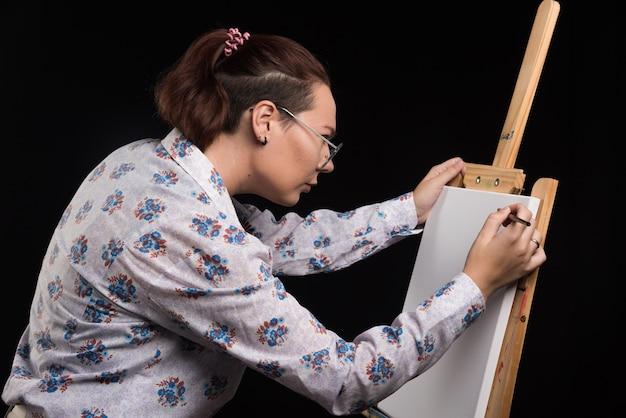 Vrouw kunstenaar schildert een afbeelding op canvas met potlood op zwarte achtergrond