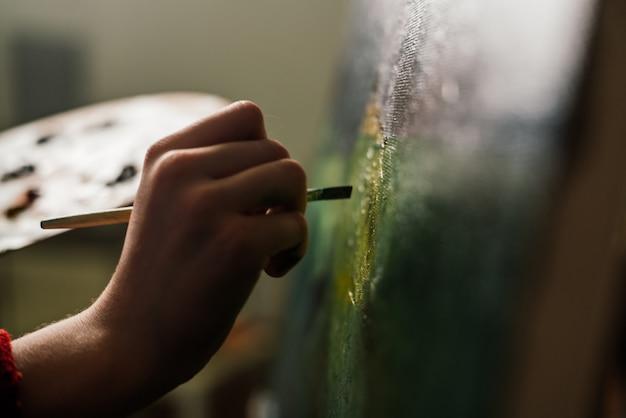 Vrouw kunstenaar schildert een foto met een penseel op een ezel