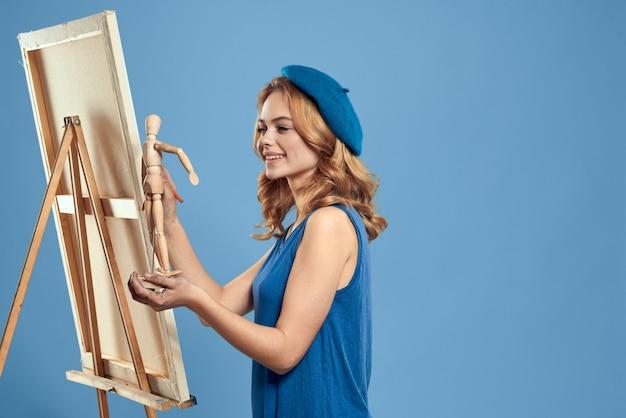 Vrouw kunstenaar schildert een foto op canvas met een ezel