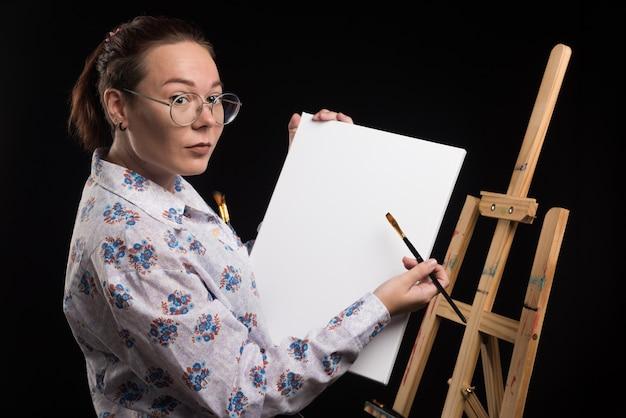 Vrouw kunstenaar toont haar canvas met penseel op zwarte achtergrond
