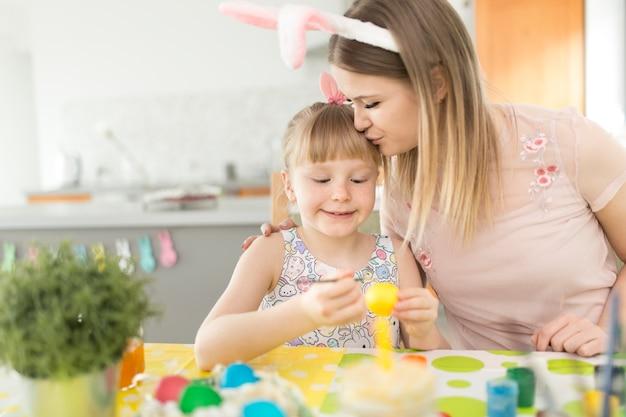 Vrouw kussende dochter het schilderen eieren