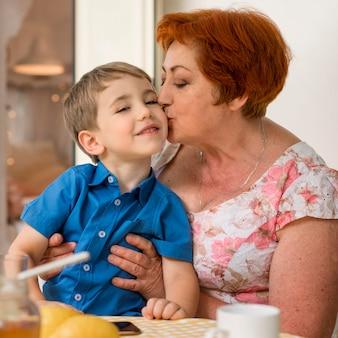 Vrouw kuste haar kleinzoon op de wang