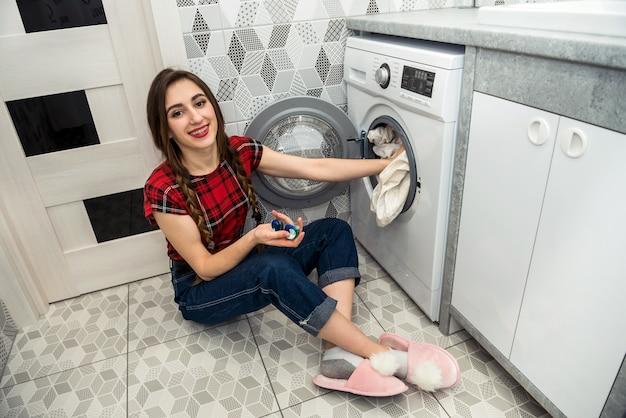 Vrouw laadt de waskleren in de wasmachine.