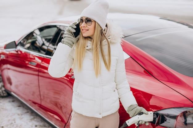Vrouw laadt rode elektrische auto op, in de winter