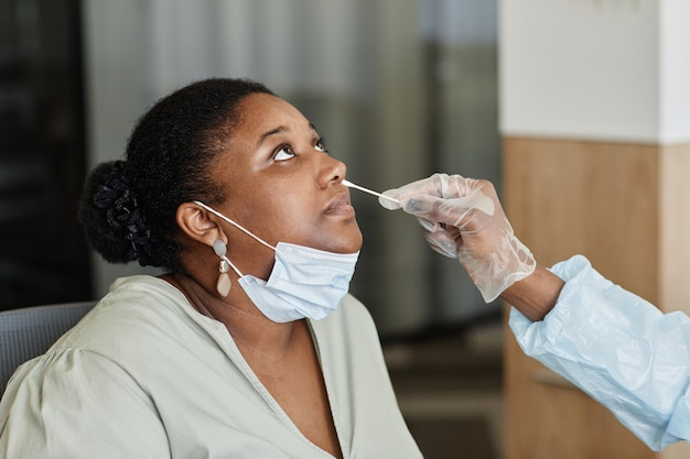 Vrouw laat dokter in beschermende handschoen een neusuitstrijkje halen om het naar het laboratorium te sturen om te testen