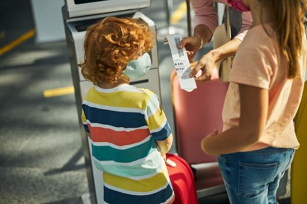 Vrouw laat kinderen een tag zien van een balie voor het vallen van tassen