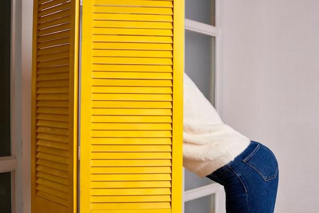 Vrouw laat zien dat ze een blauwe spijkerbroek draagt en kijkt achter een geel scherm