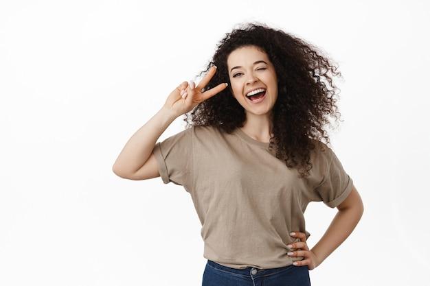 Vrouw, lachend en glimlachen, vrede v-teken tonend in de buurt van oog, kawaii pose, staande op wit