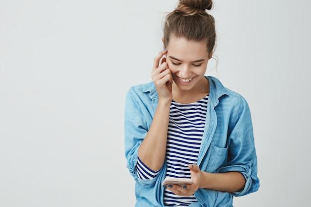 Vrouw lachend lacht vrolijk het lezen van dwaze schattige boodschap, typend antwoord op smartphone-display op zoek naar mobiel scherm geamuseerd blij, ontroerend gezicht