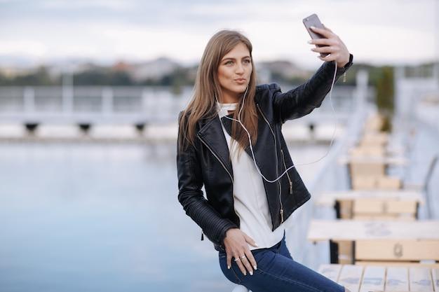 Vrouw lachend leunend op een balustrade het maken van een auto-foto