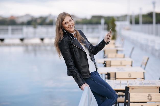 Vrouw lachend leunend op een balustrade met een mobiele telefoon in de hand