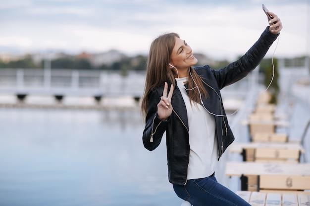 Vrouw lachend leunend op een balustrade poseren voor een foto
