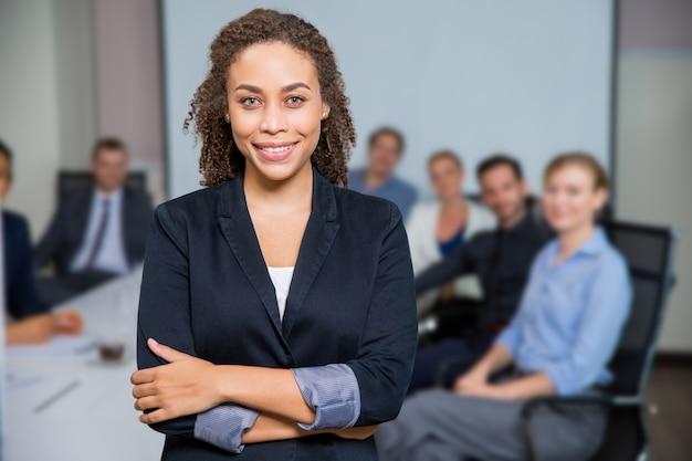 Vrouw lachend met de armen gekruist en collega's uit focus