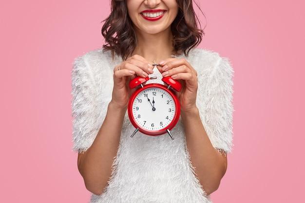 Vrouw lachend met wekker met vijf minuten voor het aftellen van het nieuwe jaar