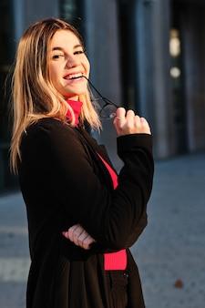 Vrouw lachend terwijl buitenshuis staan.