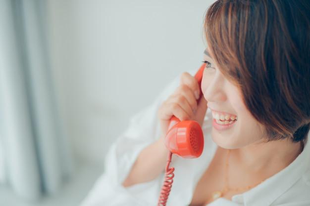 Vrouw lachend terwijl praten over een rode telefoon
