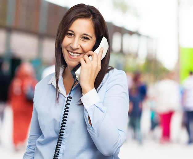 Vrouw lachend tijdens het praten aan de telefoon met vage achtergrond