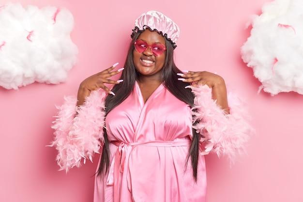 Vrouw lacht aangenaam heeft lang haar manicure gekleed in casual kamerjas douchemuts roze zonnebril houdt van zichzelf poseert binnen