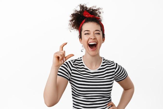 Vrouw lacht, laat een klein ding zien en grinnikt, breed glimlachend, staand in t-shirt en hoofdband op wit